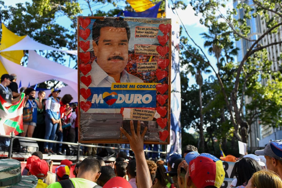 A supporter of Venezuelan President Nicolas Maduro holds a sign with Maduro's image during a march against the Inter-American Treaty of Reciprocal Assistance (TIAR) in Caracas, on 3 December 2019. [YURI CORTEZ/AFP via Getty Images]