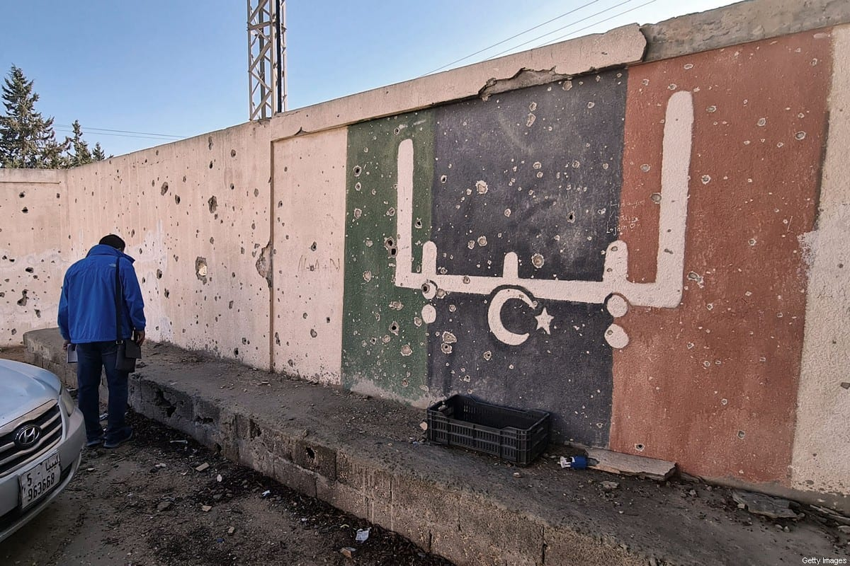 A Libyan volunteer takes part in an operation called by parents and teachers to renovate the Libya's Martyrs school, which was damaged during fighting between rival factions, in the capital Tripoli's suburb of Ain Zara, on November 19, 2020. [MAHMUD TURKIA/AFP via Getty Images]