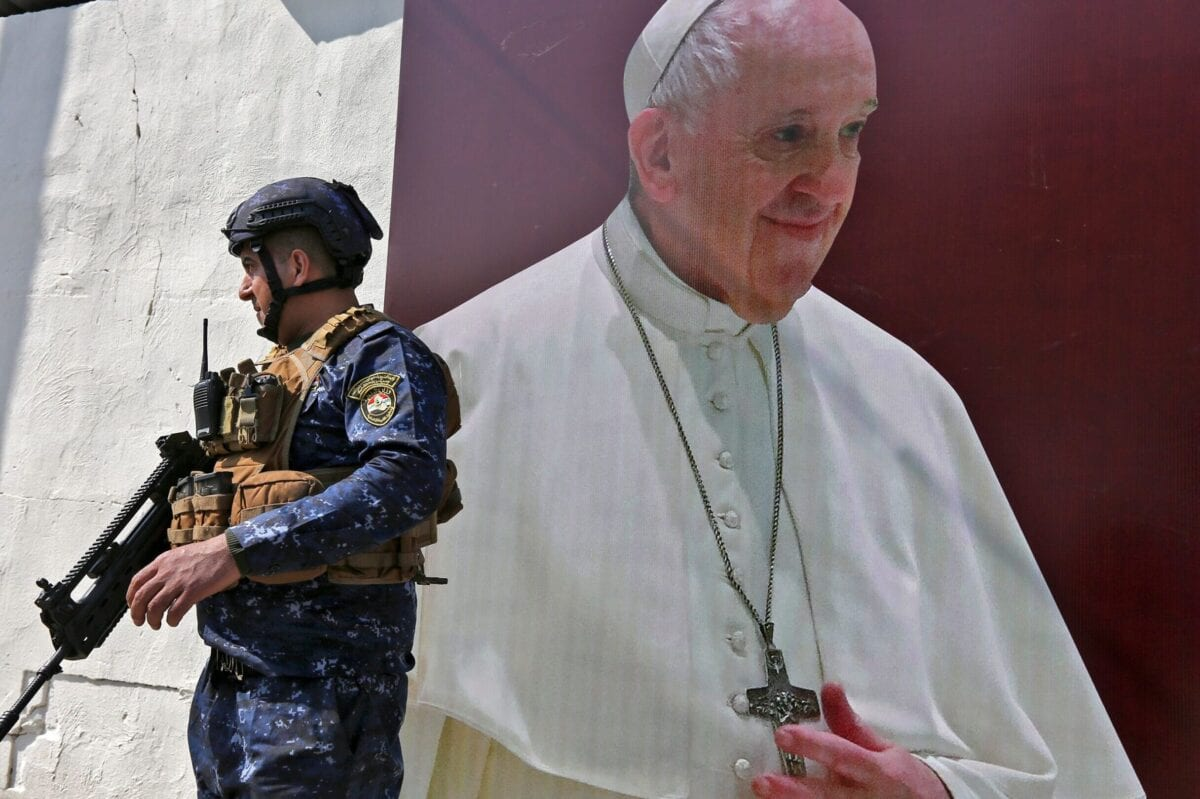 A member of the Iraqi forces stands next to a poster depicting an image of Pope Francis at the Syriac Catholic Church of Our Lady of Deliverance in the Karrada district of Iraq's capital Baghdad on March 1, 2021 amidst preparations ahead of the pontiff's visit [SABAH ARAR/AFP via Getty Images]