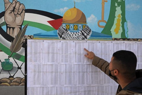 A Palestinian man looks for his name on the electoral roll at a school in Gaza City on March 3, 2021, ahead of the first Palestinian elections [MOHAMMED ABED/AFP/Getty Images]