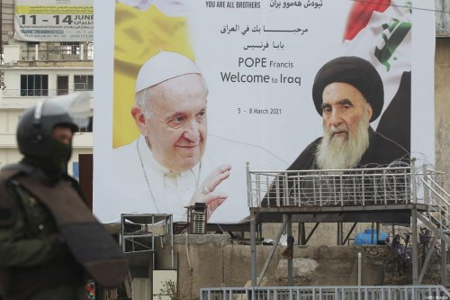An Iraqi security guard stands in front of a huge billboard bearing portraits of Pope Francis and Grand Ayatollah Ali Sistani (R) in central Baghdad on March 4, 2021, on the eve of the pontiff's first visit to Iraq. - Pope Francis begins his historic trip to war-scarred Iraq on March 5, defying security concerns and the coronavirus pandemic to comfort one of the world's oldest and most persecuted Christian communities. He is expected to meet the Shiite top cleric the next morning in the holy city of Najaf in cenral Iraq. (Photo by AHMAD AL-RUBAYE / AFP) (Photo by AHMAD AL-RUBAYE/AFP via Getty Images)