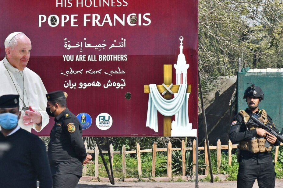 Iraqi security stand in front of a huge poster welcoming Pope Francis in Baghdad, following his arrival on March 5, 2021, at the start of the first papal visit to Iraq. - Pope Francis begins a historic 4-day trip to war-scarred Iraq on March 5, defying security concerns and the coronavirus pandemic. (Photo by Vincenzo PINTO / AFP) (Photo by VINCENZO PINTO/AFP via Getty Images)