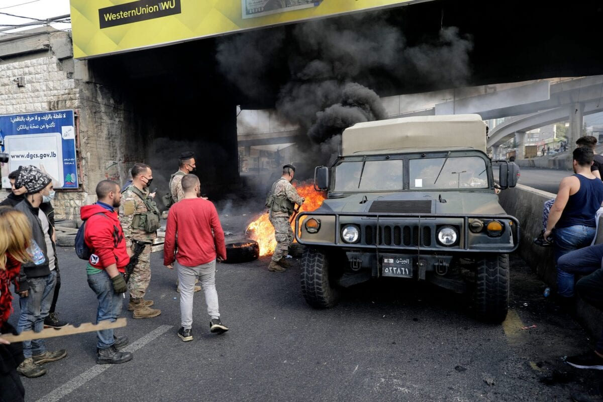 Army soldiers clear burning tires set up by anti-government protesters from the path of their vehicle at a make-shift roadblock in Zouk Mosbeh north of Lebanon's capital Beirut, on March 8, 2021 [JOSEPH EID/AFP via Getty Images]