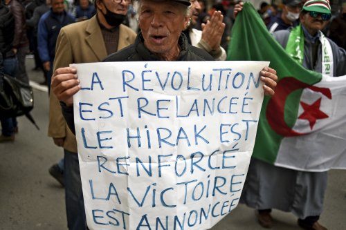 An Algerian protester carries a placard during an anti-government protest in the capital Algiers on March 9, 2021 [RYAD KRAMDI/AFP via Getty Images]