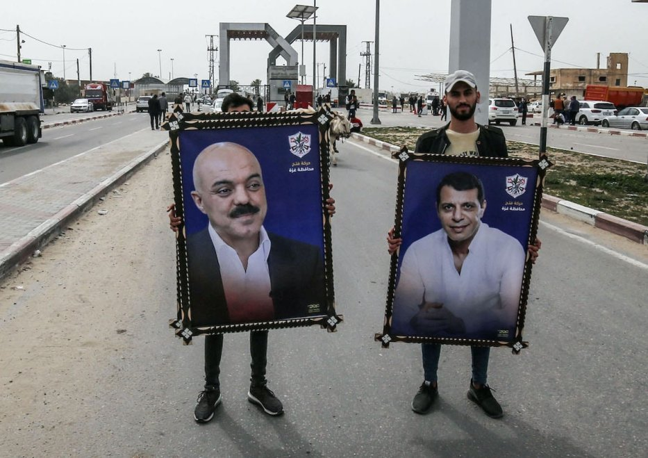 Palestinians lift portraits of exiled Fatah movement's former security chief Mohammed Dahlan (R) and politician Samir al-Mashharawi in the southern Gaza Strip, on March 11, 2021. [SAID KHATIB/AFP via Getty Images]