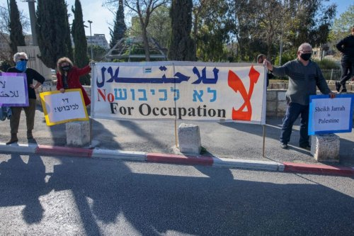 Palestinian, Israeli, and foreign activists lift banners and placards during a demonstration against Israeli occupation and settlement activity in the Palestinian Territories and east Jerusalem, in Jerusalem's Palestinian Sheikh Jarrah neighbourhood, on March 19, 2021 [AHMAD GHARABLI/AFP via Getty Images]
