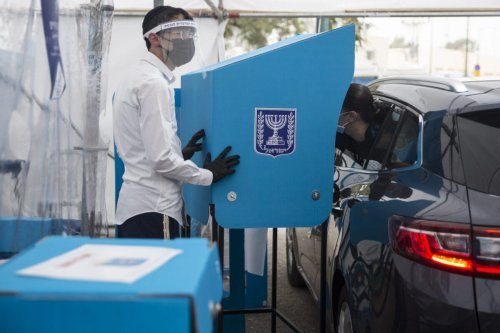 RAMAT GAN, ISRAEL - MARCH 23: A woman casts her vote at a drive-in polling center for people on quarantine or tested positive for COVID-19 as Israelis head to the polls on March 23, 2021 in Ramat Gan, Israel. Prime Minister Benjamin Netanyahu's Likud party is poised to win the most seats, but will likely need to form a coalition with other parties to form a government. In this election, the fourth in a two-year period, Yair Lapid has emerged as the principal opposition candidate. One potential outcome of today's vote is that neither Lapid nor Netanyahu can form a government, leading to yet another election. (Photo by Amir Levy/Getty Images)