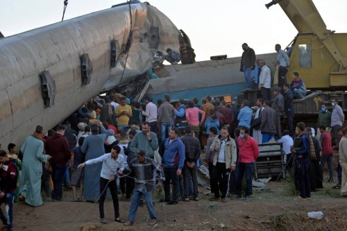People gather around the wreckage of two trains that collided in the Tahta district of Sohag province, reportedly killing at least 19 people and injuring scores of others, on March 26, 2021 [AFP via Getty Images]
