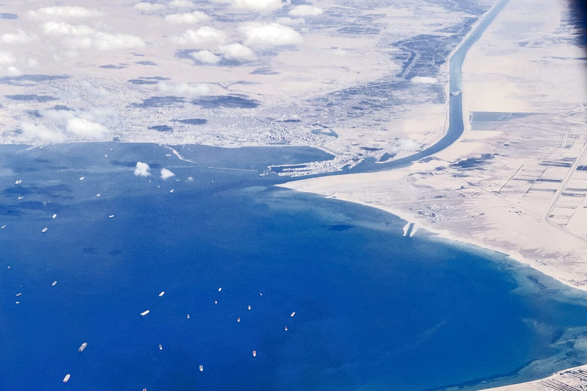 "An aerial view taken on March 27, 2021 from the porthole of a commercial plane shows stranded ships waiting in queue in the Gulf of Suez to cross the Suez Canal at its southern entrance near the Red Sea port city of Suez, as the waterway remains blocked by the Panama-flagged container ship ""MV Ever Given"", which has remained wedged sideways about six kilometres north of the canal's entrance impeding all flowing traffic since March 23. - The owner of a megaship blocking the canal hopes to refloat it as early as today, as the crisis forced companies to re-route services from the vital shipping lane around Africa. The MV Ever Given, which is longer than four football fields, has been wedged diagonally across the span of the canal since four days, blocking the waterway in both directions. (Photo by Mahmoud KHALED / AFP) (Photo by MAHMOUD KHALED/AFP via Getty Images)"