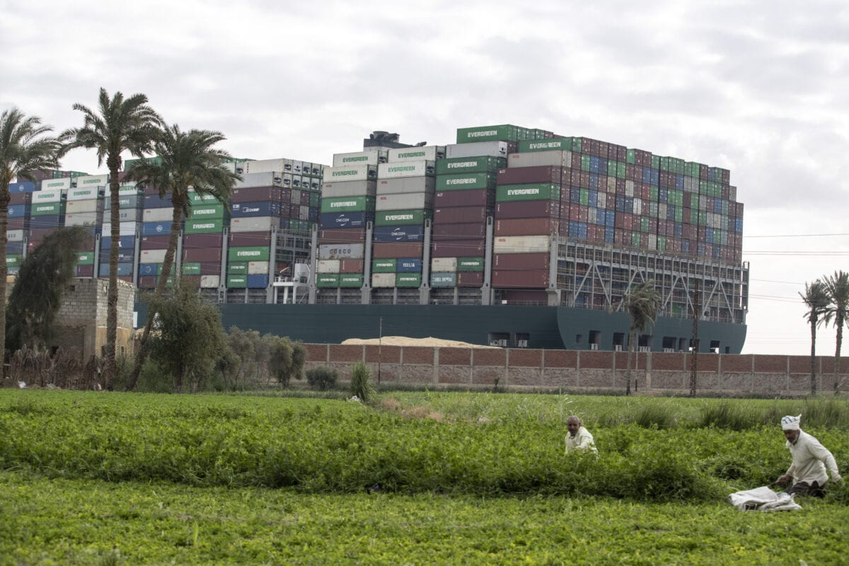 SUEZ, EGYPT - MARCH 28: The container ship, the Ever Given, is seen from a village near the Suez Canal on March 28, 2021 in Suez, Egypt. Work continues to free the Ever Given, a huge container ship stuck sideways in Egypt's Suez Canal. The ship ran aground in the canal on March 23, after being caught in 40-knot winds. Dredgers have been working on the port side of the ship in an attempt to remove sand and mud and dislodge the vessel. The Suez Canal is one of the worlds busiest shipping lanes and the blockage has created a backlog of vessels at either end, raising concerns over the impact the accident will have on global shipping and supply chains. (Photo by Mahmoud Khaled/Getty Images)
