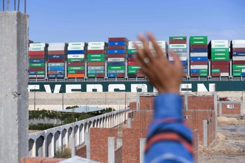 A man waves at the Panama-flagged MV 'Ever Given' container ship as it is tugged in Egypt's Suez Canal after it was fully dislodged from the banks, near Suez city, on March 29, 2021 [AHMAD HASSAN/AFP via Getty Images]