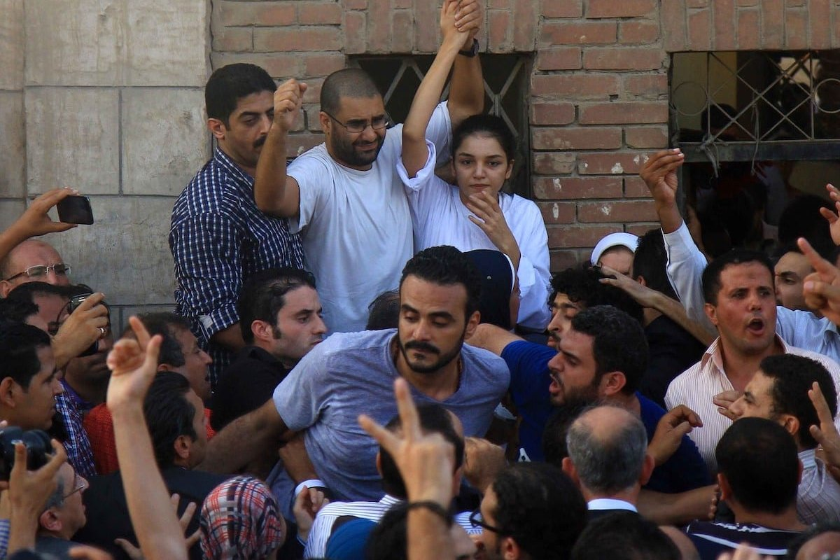 Jailed Egyptian sibling activists Alaa Abdel Fattah (2nd L) and Sanaa Seif (R) gesture after they were granted permission by authorities to attend the funeral of their father, prominent Egyptian human rights lawyer Ahmed Seif el-Islam, in Cairo on 28 August 2014. [HASAN MOHAMED/AFP via Getty Images]