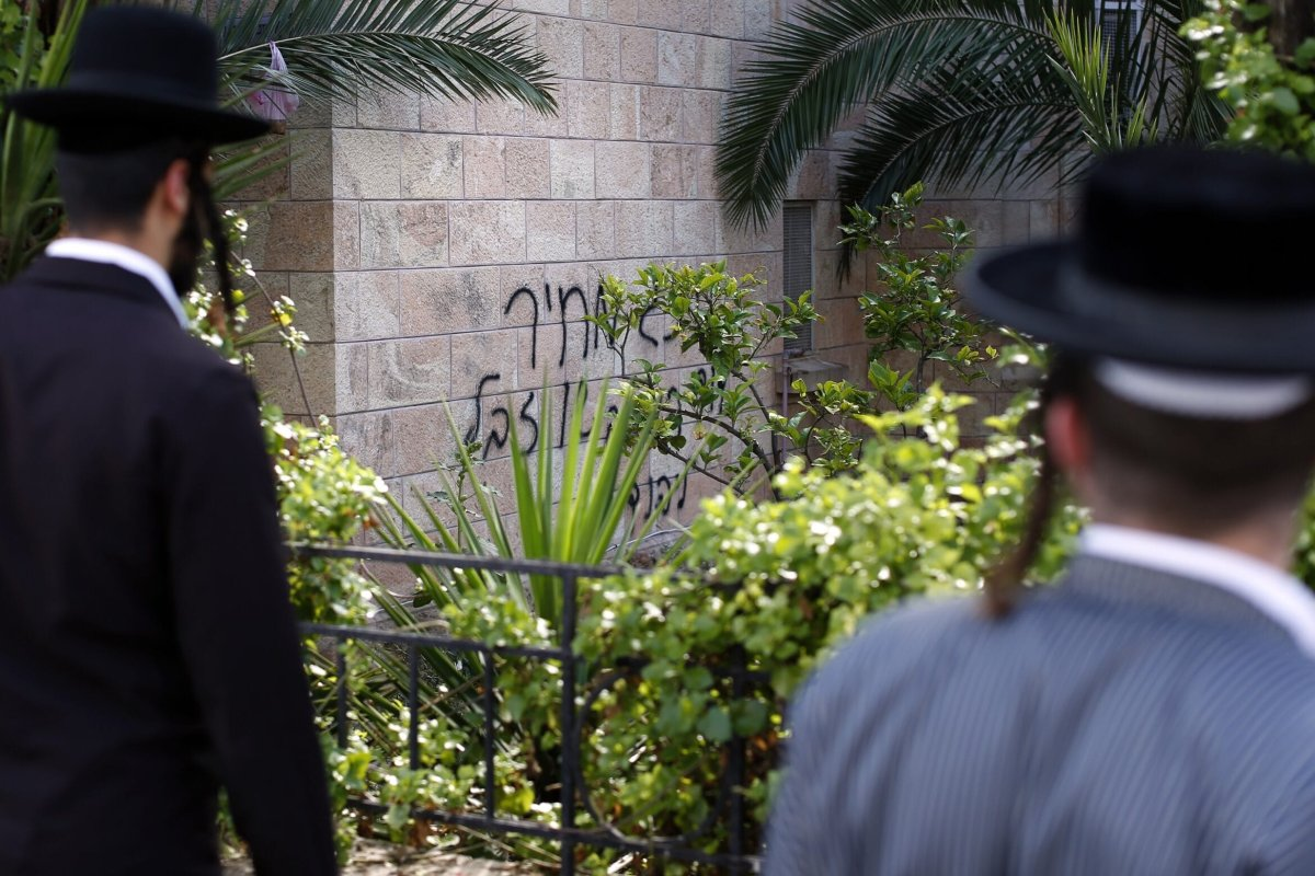 "Two Ultra Orthodox Jews look at graffiti on the wall of a church reading in Hebrew ""King David king of the Jews and Jesus is garbage, Price tag"" on May 9, 2014 in Jerusalem [THOMAS COEX/AFP via Getty Images]"