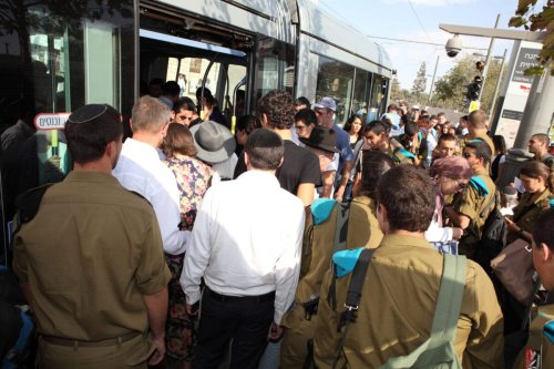 A crowd of people, men women, soldiers and civilians, Jews and Arabs push to board the Light Train or Light Rail at the Central Bus Station, Jerusalem, Israel, October 6, 2014 [Dan Porges/Getty Images]