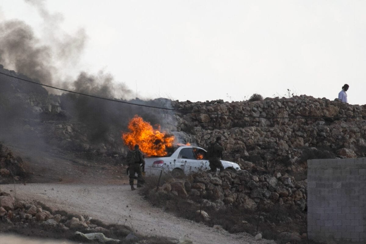 Israeli soldiers walk past a burning car in the Palestinian village of Qusra in the occupied West Bank on September 26, 2020 [JAAFAR ASHTIYEH/AFP via Getty Images]