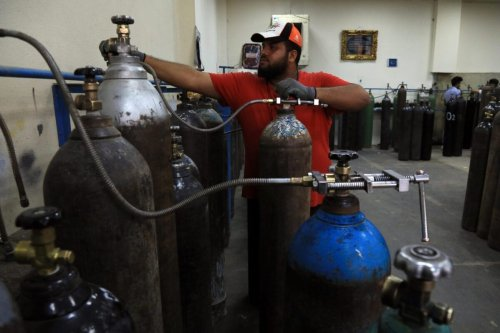 An Iraqi worker fills an oxygen tanks at a filling station in Arbil, the capital of the northern Iraqi Kurdish autonomous region, on November 3, 2020. - In Arbil like all over Iraq, people prefer to rely on oxygen tanks and receiving medicine at home rather than going to hospitals that are run down, with outdated or broken equipment and staff often poorly trained and overworked. Almost half a million Iraqis are infected by the virus which killed more than 11,000 of them. (Photo by SAFIN HAMED / AFP) (Photo by SAFIN HAMED/AFP via Getty Images)