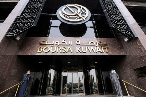 Traders, mask-clad due to the COVID-19 coronavirus pandemic, stand at the entrance of the Boursa Kuwait (Kuwait's national stock exchange) building on 1 December 2020. [YASSER AL-ZAYYAT/AFP via Getty Images]