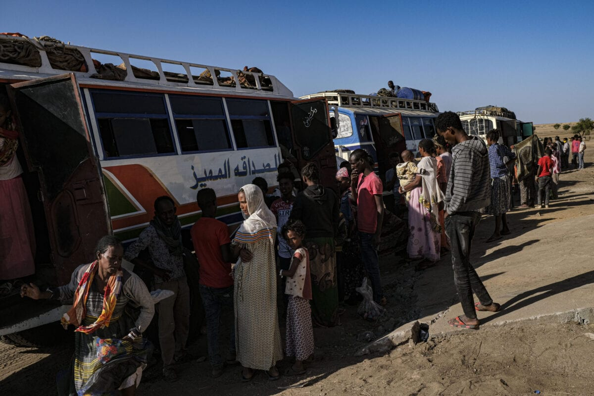 Refugees from the Tigray region of Ethiopia board buses to a Um Rakuba refugee camp after spending days to weeks at a UNHCR reception center located in the east Sudanese border village of Hamdayet on December 7, 2020 in Hamdayet, Sudan [Byron Smith/Getty Images]