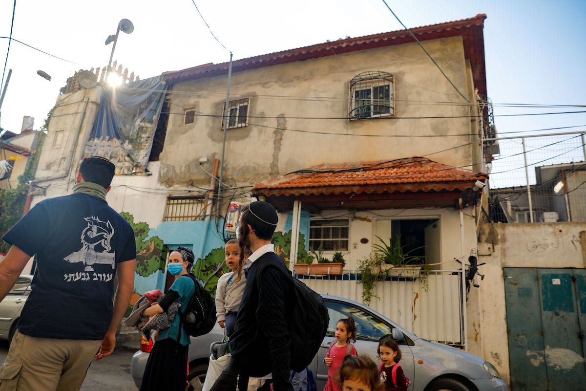 Israeli settlers walk in front of a home inhabited by Palestinians, in the predominantly Arab neighbourhood of Silwan in east Jerusalem, on 9 November 2020. [AHMAD GHARABLI/AFP via Getty Images]