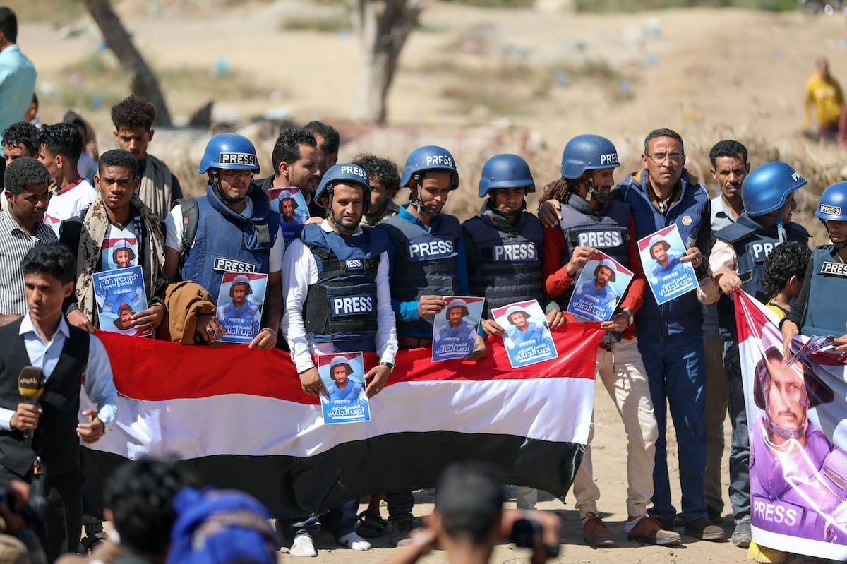 Journalists and mourners lift placards and banners during the funeral of TV reporter Adib al-Janani who was killed in an attack on Aden airport, in Yemen's third city of Taez on 2 January 2021. [AHMAD AL-BASHA/AFP via Getty Images]