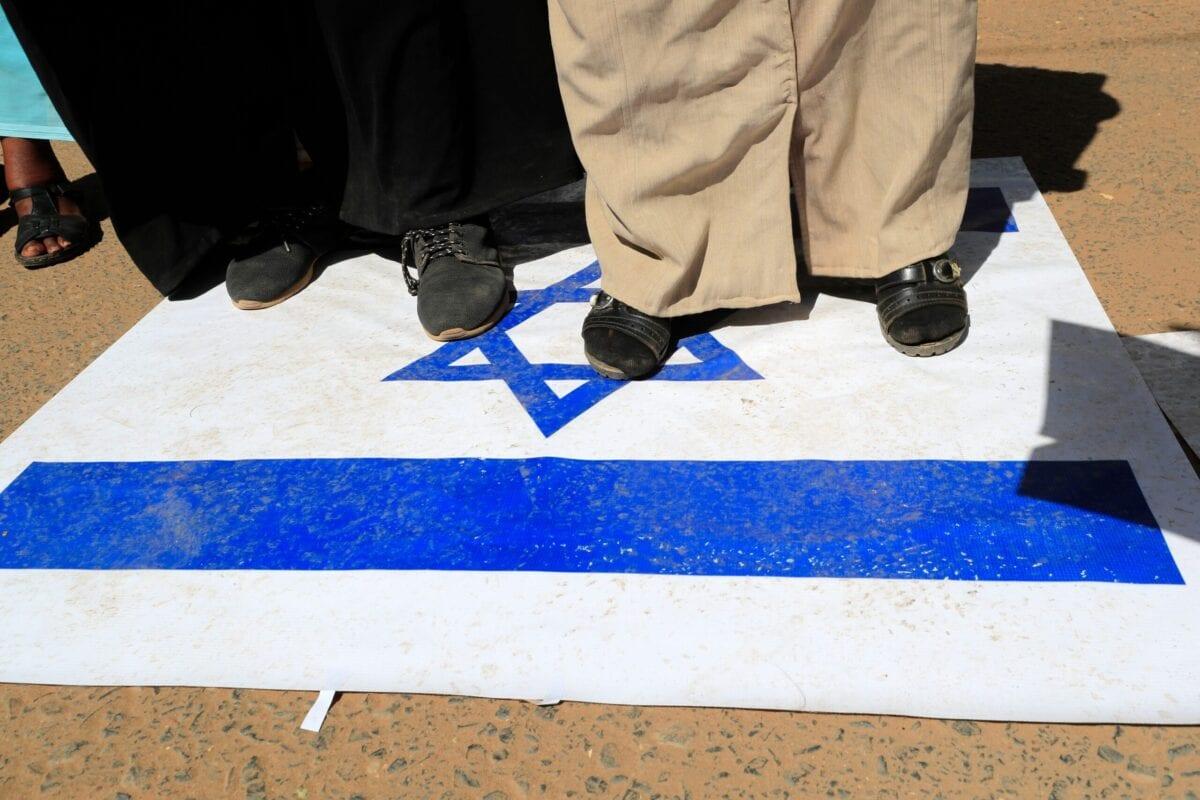 Sudanese demonstrators stem on an Israeli flag in Khartoum, on January 17, 2021 [ASHRAF SHAZLY/AFP via Getty Images]