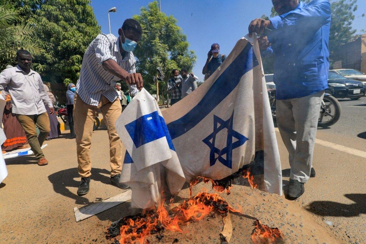 Sudanese demonstrators burn an Israeli flag on January 17, 2021 [ASHRAF SHAZLY/AFP via Getty Images]