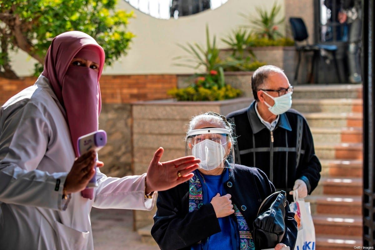 An Egyptian medical worker checks people's temperatures on March 4, 2021 in Cairo [KHALED DESOUKI/AFP via Getty Images]