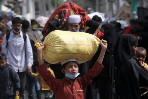 Rohingya refugees carry their belongings as they leave a Rohingya refugee camp in Jammu on March 7, 2021. (Photo by Rakesh BAKSHI / AFP) (Photo by RAKESH BAKSHI/AFP via Getty Images)