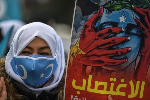 Members of Women Muslim Uighur minority hold placards and flags as they demonstrate on March 8, 2021 [OZAN KOSE/AFP via Getty Images]