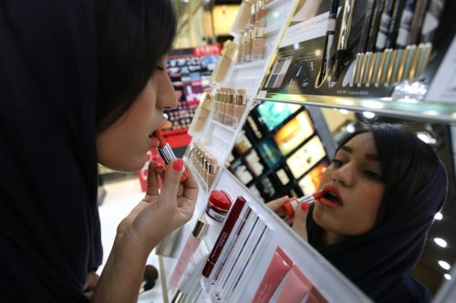 TO GO WITH AFP STORY BY CYRIL JULIEN An Iranian woman tries on a lipstick at a cosmetics shop in northern Tehran on May 6, 2014. Under the compulsory veil and despite hard times, Iranian women are unrestrained in showing off one feature on which they feel a need to spend money. Their faces. Everyday wearing of makeup is probably more common in Iran, an Islamic republic, than in some liberal western countries. It is a rare opportunity to parade one's beauty without fear of official censure. AFP PHOTO/ATTA KENARE (Photo credit should read ATTA KENARE/AFP via Getty Images)