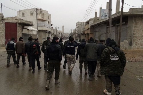 Opposition fighters from the Syrian militant group Ahrar Al-Sham brigade, walk in the Shiekh Lutfi neighbourhood of the northern Syrian city of Aleppo during ongoing clashes with government forces on 27 January 2014. [BARAA AL-HALABI/AFP via Getty Images]