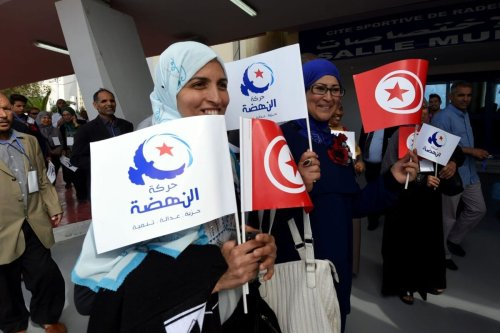 Supporters of Tunisia's Islamist Ennahdha Party wave the national flag and the party flag on May 20, 2016 during the opening of Ennahdha's three-day congress in Tunis [FETHI BELAID/AFP via Getty Images]