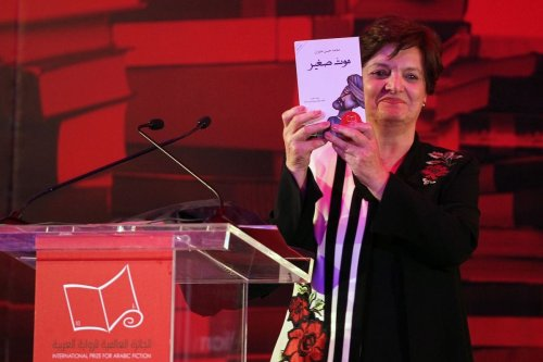 Palestinian novelist and chair of the judging committee Sahar Khalifeh poses for a photo with the winning book of the 2017 International Prize for Arabic Fiction book by Saudi Arabian writer Mohammed Hasan Alwan in Abu Dhabi on 25 April 2017. [SAEED BASHAR/AFP via Getty Images]