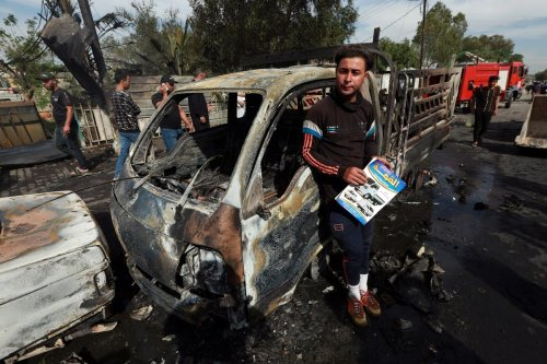 BAGHDAD, IRAQ - APRIL 15: People inspect after an explosive device placed under a vehicle exploded in the al-Habibiya area of al-Sadr city, eastern Baghdad, Iraq on April 15, 2021. One person was killed and 14 others were injured as three other vehicles damaged in the bomb blast. ( Murtadha Al-Sudani - Anadolu Agency )