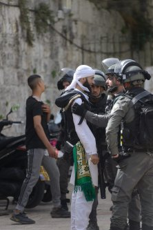Israeli police take Palestinian youths, who were standing guard to prevent fanatic Jews to raid the Masjid al-Aqsa Compound, into custody in East Jerusalem on May 10, 2021 [Muath Khatib/Anadolu Agency]