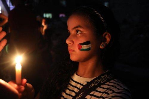 Palestinian children light candles in memory of Abu Hattab family killed in the Israeli air strikes on Gaza, on 23 May 2021 [Ashraf Amra/Anadolu Agency]
