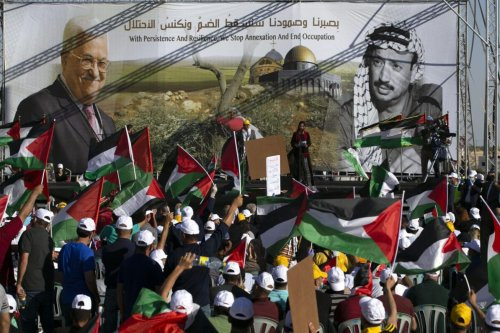 Palestinians wave flags during a big rally called by Palestinian Authority's Fatah party to protest against Israel's plan to annex parts of the occupied West Bank, in Jericho on June 22, 2020 [ABBAS MOMANI/AFP via Getty Images]