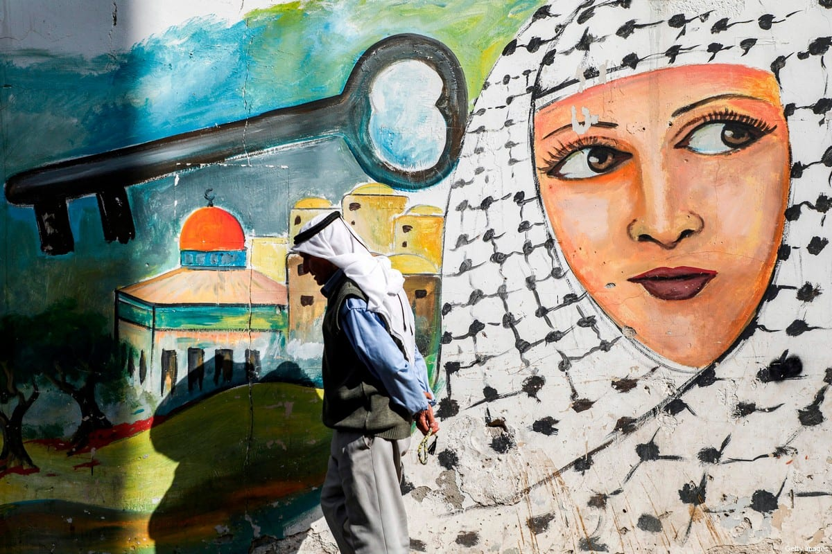 A man walks past a graffiti mural depicting a Palestinian woman clad in a keffiyeh scarf next to a depiction of a key above the Dome of the Rock, in the Jenin camp for Palestinian refugees in the north of the occupied West Bank on September 10, 2020 [JAAFAR ASHTIYEH/AFP via Getty Images]