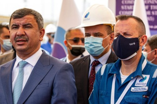 Malcolm Mayes (R), managing director of the Basra Gas Company (BGC), and Iraq's oil minister Ihsan Abdul Jabbar (L) attend the inauguration of a new gas compressor station in the Rumaylah oil field near Iraq's southern port city of Basra on February 28, 2021 [HUSSEIN FALEH/AFP via Getty Images]