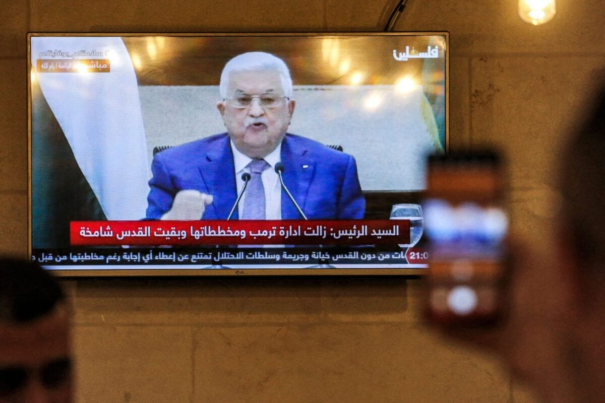 A man uses his phone to film a televised speech by Palestinian president Mahmud Abbas regarding the upcoming Palestinian elections at a coffee shop in the city of Hebron in the occupied West Bank on April 29, 2021 [HAZEM BADER/AFP via Getty Images]