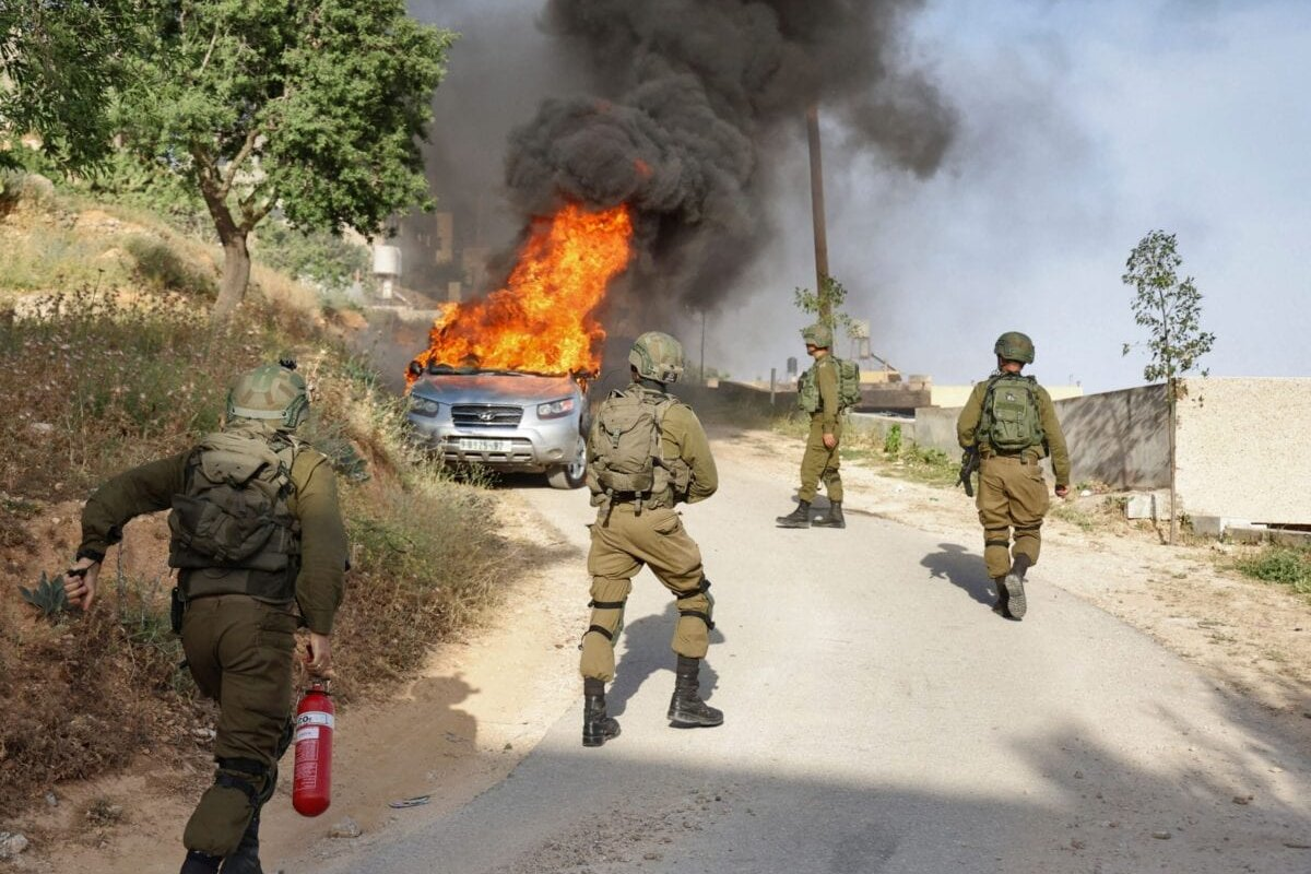 An Israeli soldier tries to extinguish flames in a burning Palestinian vehicle during a security operation in the village of Aqraba, east of Nablus in the occupied-West Bank, on May 3, 2021 [JAAFAR ASHTIYEH/AFP via Getty Images]