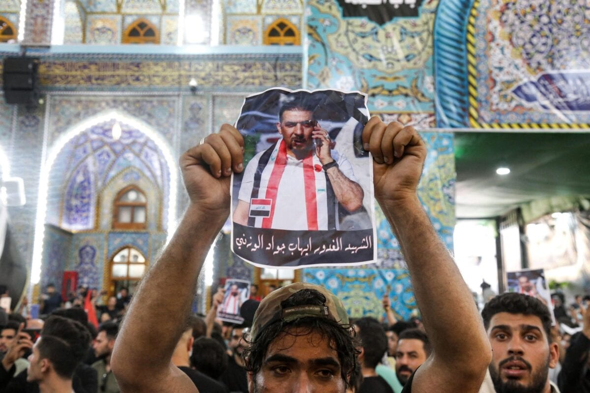 A mourner holds up a poster showing assassinated Iraqi anti-government activist Ihab al-Wazni during his funeral at the Imam Hussein Shrine in the central holy shrine city of Karbala on May 9, 2021 [MOHAMMED SAWAF/AFP via Getty Images]