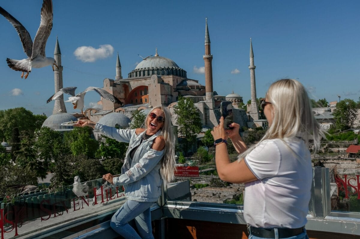 Tourists taking pictures near the Hagia Sophia Mosque at Sultanahmet in Istanbul on May 9, 2021 [BULENT KILIC/AFP via Getty Images]