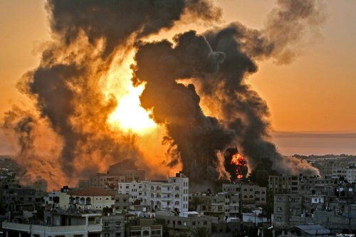 A fire rages at sunrise in Khan Yunish following an Israeli airstrike on targets in the southern Gaza strip, early on May 12, 2021 [YOUSSEF MASSOUD/AFP via Getty Images]
