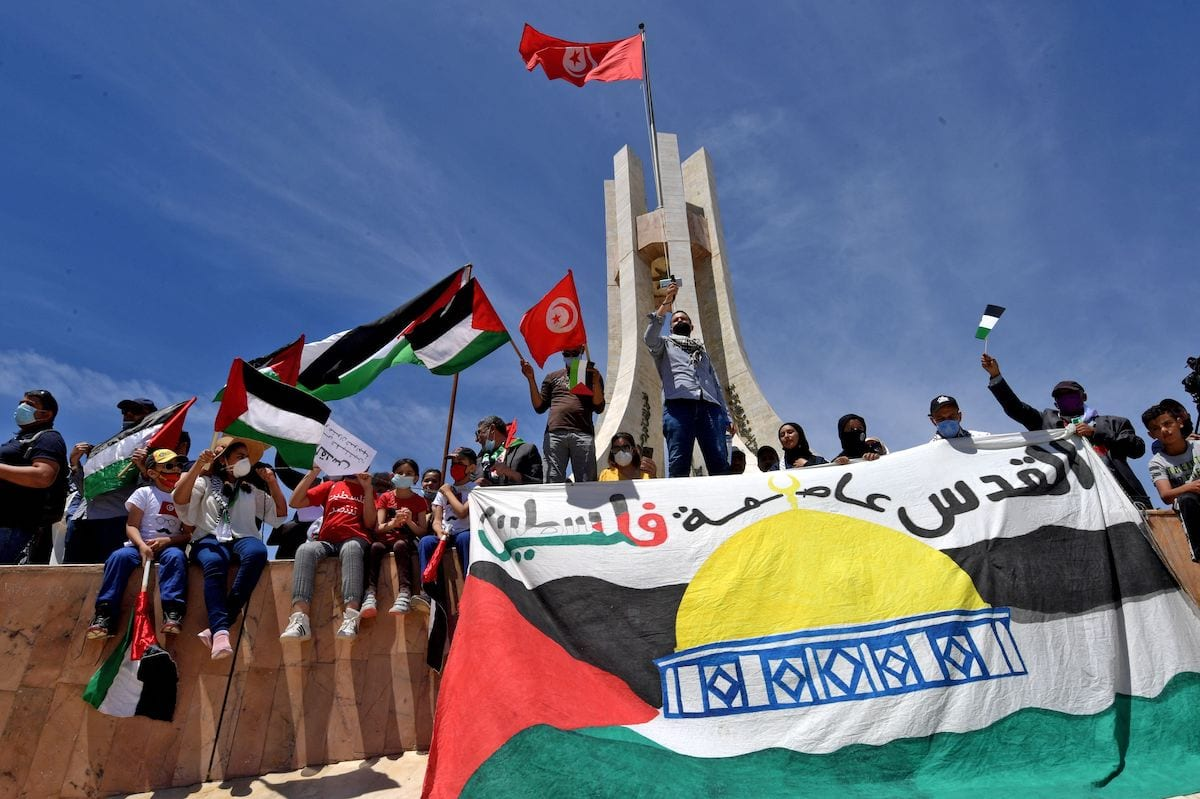 """Tunisians wave the Palestinian flag during a demonstration in the capital Tunis, on 15 May 2021, to mark the 73rd anniversary of the Nakba, the """"catastrophe"""" of Israel's creation in 1948, and to express their solidarity with the Palestinian people. [FETHI BELAID/AFP via Getty Images]"""