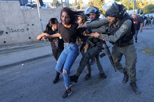Israeli security forces try to detain a Palestinian woman in the east Jerusalem neighbourhood of Sheikh Jarrah on May 15, 2021 [EMMANUEL DUNAND/AFP via Getty Images]