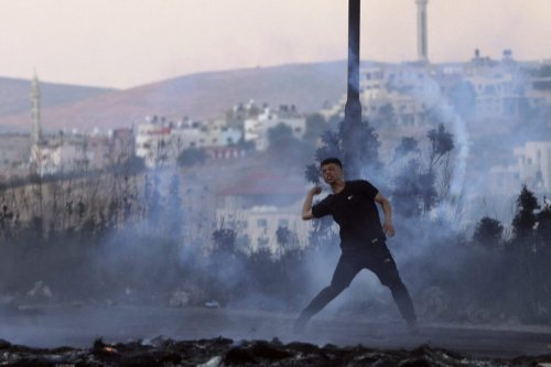 A Palestinian protester throws a stone in the occupied West Bank, on May 17, 2021 [JAAFAR ASHTIYEH/AFP via Getty Images]