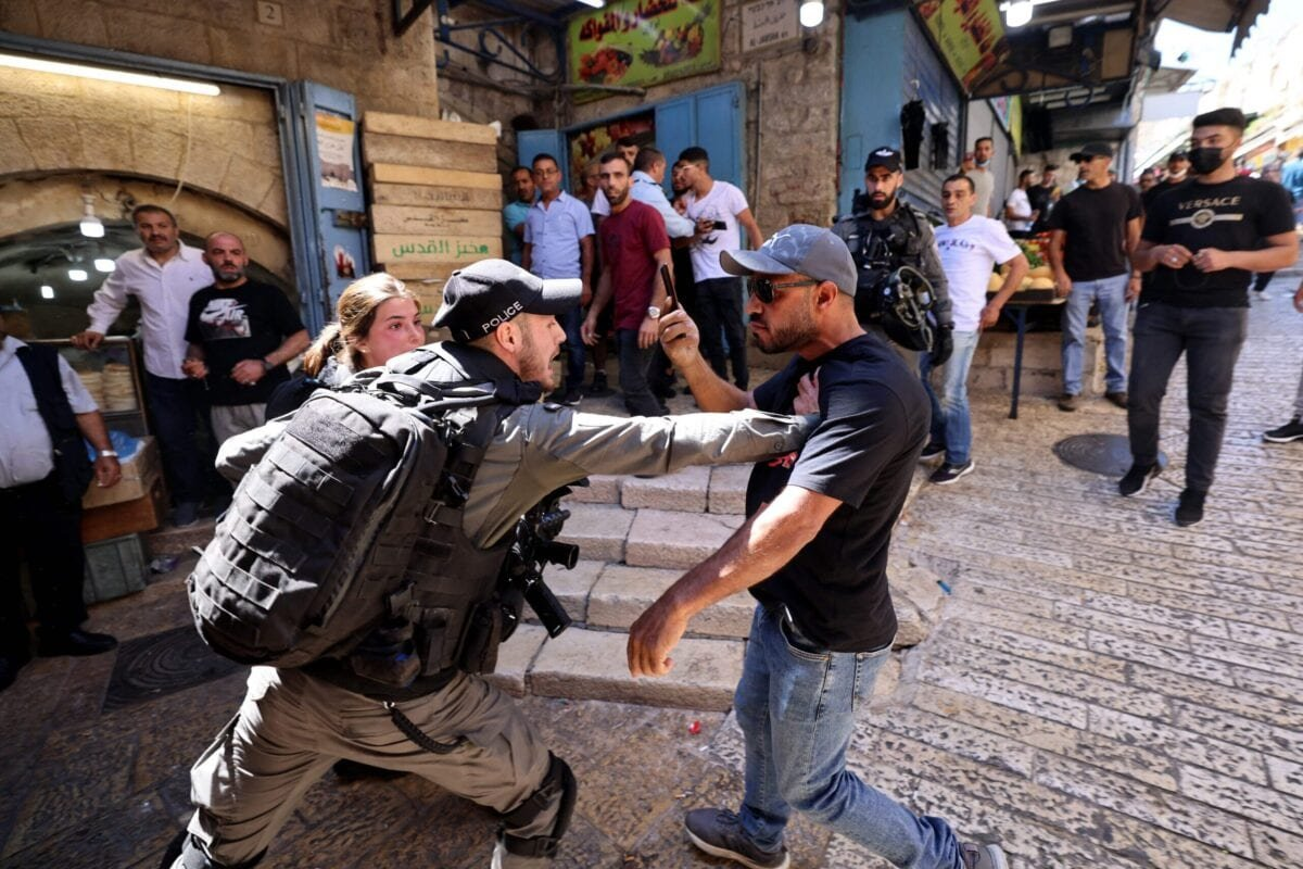 An Israeli border police member confronts a Palestinian man during protests against Israel's occupation and its air campaign on the Gaza strip, at Damascus Gate in East Jerusalem, on May 18, 2021 [EMMANUEL DUNAND/AFP via Getty Images]