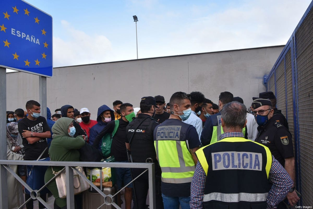 Spanish policemen stand next to migrants waiting to cross the border back to Morocco at the Spanish enclave of Ceuta on 20 May 2021 [ANTONIO SEMPERE/AFP/Getty Images]