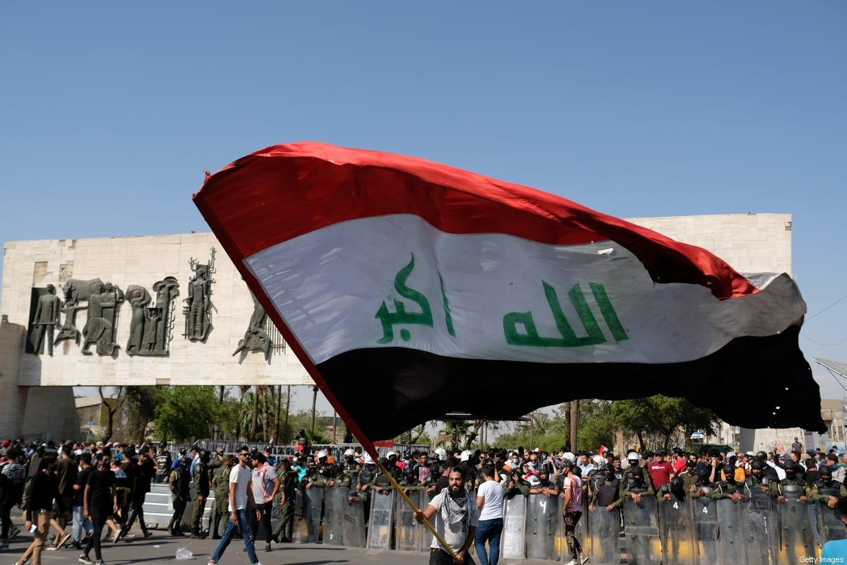 Iraqis waving the Iraqi flag in Al Tahrir Square on May 25, 2021 in Baghdad, Iraq [Taha Hussein Ali/Getty Images]
